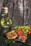 Grilled meat with salad and vegetables. Steak and salad on a wooden table Royalty Free Stock Images