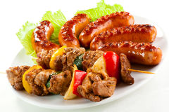 Grilled meat and sausages. Grilled meat, sausages and vegetables royalty free stock photos