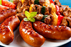 Grilled meat and sausages. Grilled meat, sausages and vegetables royalty free stock photo