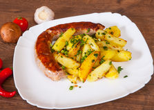 Grilled meat sausages with fried potatoes Stock Photography