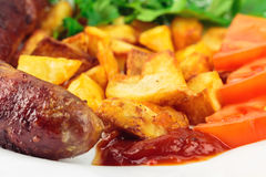 Grilled meat sausages with fried potatoes, sliced tomatoes, fresh produce and ketchup in plate, selective focus Royalty Free Stock Photo