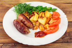Grilled meat sausages with fried potatoes, sliced tomatoes, fresh produce and ketchup in plate on wooden table Stock Photography