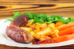 Grilled meat sausages with fried potatoes, sliced tomatoes, fresh produce and ketchup in plate on wooden table Royalty Free Stock Images