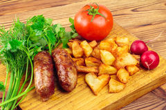 Grilled meat sausages with fried potatoes, tomato and fresh produce on wooden board.  Stock Photo