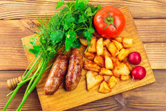 Grilled meat sausages with fried potatoes, tomato and fresh produce on wooden board, top view.  Royalty Free Stock Images