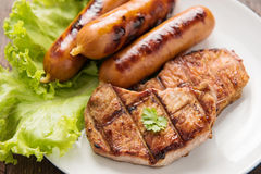 Grilled meat, sausages and vegetables on dish close up. Grilled meat, sausages and vegetables on dish close up stock image