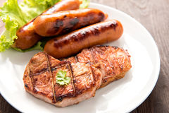 Grilled meat, sausages and vegetables on dish close up stock image