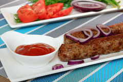 Grilled meat sausages with vegetables and ketchup. Kebab Royalty Free Stock Photography