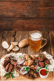 Grilled meat served with beer on rustic table. Appetizing meal in pub with fresh grilled meat assortment, pita bread, buns, and mug of cold light beer served on Royalty Free Stock Photography