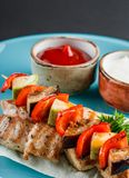 Grilled meat shish and vegetables kebab on skewers with sauce in plate over dark background. Healthy food. Hot meat dishes,. Shashlik food stock photo