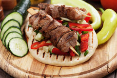 Grilled meat skewer with pita bread. Grilled meat skewer served with salad over pita bread Royalty Free Stock Photos