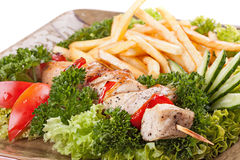 Grilled meat skewers with french  fries. Stock Photo