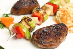 Grilled meat and skewers on plate Stock Photography