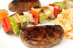 Grilled meat and skewers on plate Royalty Free Stock Images