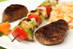 Grilled meat and skewers on plate Stock Photos