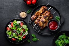 Grilled meat skewers, shish kebab and healthy vegetable salad of fresh tomato, cucumber, onion, spinach, lettuce and sesame on bla. Ck background, top view Stock Photo