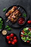 Grilled meat skewers, shish kebab and healthy vegetable salad of fresh tomato, cucumber, onion, spinach, lettuce and sesame on bla. Ck background, top view Royalty Free Stock Photo