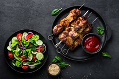 Grilled meat skewers, shish kebab and healthy vegetable salad of fresh tomato, cucumber, onion, spinach, lettuce and sesame on bla. Ck background, top view Stock Images