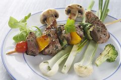 Grilled meat skewers and vegetables Stock Image