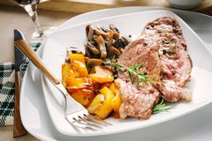 Grilled meat slices with champignon mushrooms and yellow peppers Stock Photos