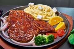 Grilled meat and spaghetti on plate Royalty Free Stock Images