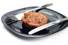 Grilled meat steak at black plate with fork and knife Stock Photos