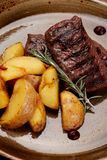 Grilled Meat Steak and Potatoes Rosemary on Plate stock image