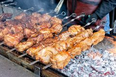Grilled meat at street festival. huge pieces of meat cooking at barbeque with coal and fire.  stock photos