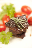 Grilled meat. Strongly roasted beef garnished with herbs Stock Photos