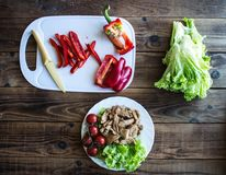 Grilled meat tomatoes on a plate with pepper knife and salad stock images