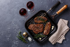 Grilled meat Top Blade steaks on frying pan. And red wine on dark background stock image