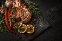 Grilled meat and vegetables on a black rustic background. stock image