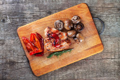 Grilled meat and vegetables on the cutting board Stock Photo