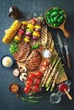 Grilled meat and vegetables on rustic stone plate Royalty Free Stock Image