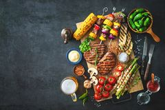 Grilled meat and vegetables on rustic stone plate Royalty Free Stock Photography