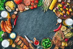 Grilled meat and vegetables on rustic stone plate. Barbecue menu. Grilled meat and vegetables on rustic stone plate with copy space for text Royalty Free Stock Photo