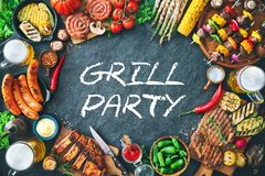 Grilled meat and vegetables on rustic stone plate Stock Photos