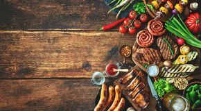 Grilled meat and vegetables on rustic wooden table royalty free stock images