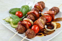 Grilled meatball skewers. With basil leaves and cherry tomatoes on dish Royalty Free Stock Photo