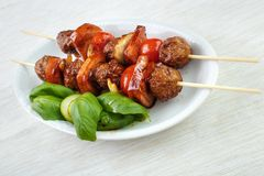 Grilled meatball skewers. With basil leaves on dish Royalty Free Stock Image