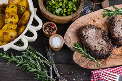 Grilled medium rare beef steak with herbs on rustic table Stock Images