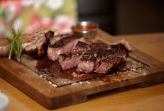 Grilled medium rare steak with coarse salt and rosemary on a wooden board stock photography
