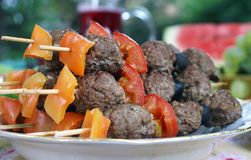 Grilled meetballs with vegetables on wooden sticks. Meatballs with vegetables on wooden sticks, grilled during alfresco dinner, blur background, closeup, focus Stock Images