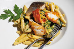 Grilled mixed fish with penne and spinach Stock Photo