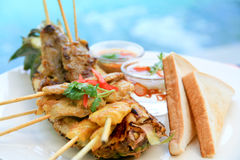 Grilled mixed satay. Grilled mixed meats satay with sauce and toasted bread Royalty Free Stock Photo