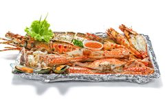 Grilled Mixed Seafood Big Set: Lobster Fish Blue Clabs Big Shrimps Mussels Clams Calamari Squids with pieces of lemon & vegetable. On white background with stock photo