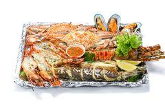 Grilled Mixed Seafood Medium Set contain 1 Lobster, 1 Fish, 2 Blue Clabs, 3 Big Shrimps, 3 Mussels Clams, 3 Calamari Squids with 2. Pieces of lemon & vegetables stock images