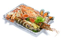 Grilled Mixed Seafood platter Set : Lobster, Fish, Blue Clab, Big Prawn, Mussel Clam, Calamari Squids with pieces of lemon &. Vegetable isolated on white stock photography