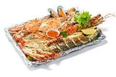 Grilled Mixed Seafoods platter Set contain Lobsters Fish Blue Clabs Big Shrimps Mussels Clams Calamari Squids with pieces of lemon. & vegetables isolated on royalty free stock images
