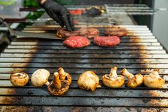 Grilled mushrooms with meat on the stove stock image